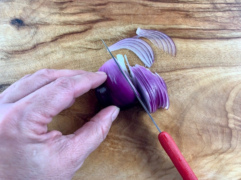 THINLY SLICING RED ONION ON WOODEN BOARD WITH RED KNIFE