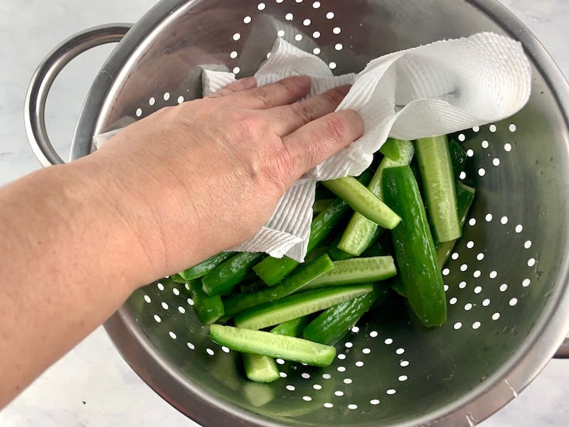 PATTING SWEATED CUKES IN COLANDER WITH KITCHEN TOWEL TO DRY