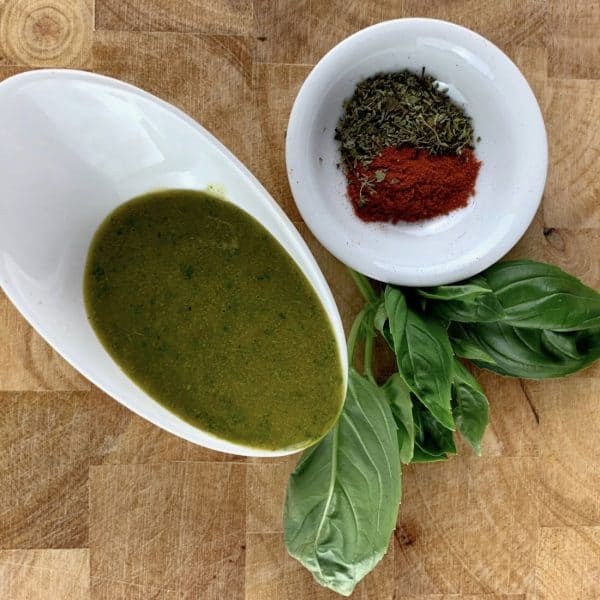 ITALIAN VINAIGRETTE IN A WHITE BOWL WITH FRESH BASIL AND PAPRIKA AND DRIED OREGANO IN A WHITE BOWL ON THE SIDE