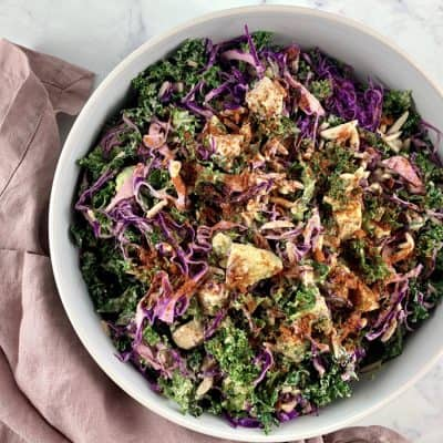 KALE AVOCADO SALAD IN A WHITE BOWL WITH DUSTY PINK NAPKIN ON THE SIDE
