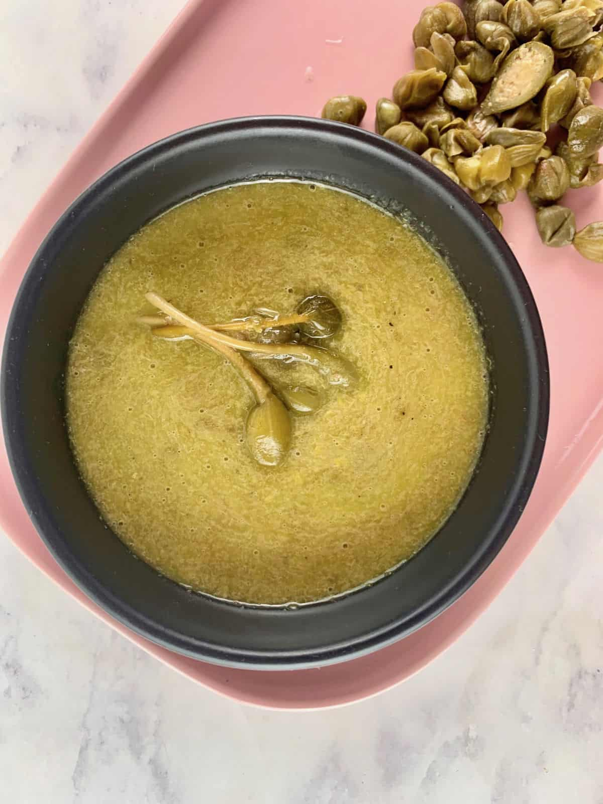 LEMON CAPER DRESSING IN BLACK BOWL ON PINK PLATTER WITH CAPERS ON THE SIDE