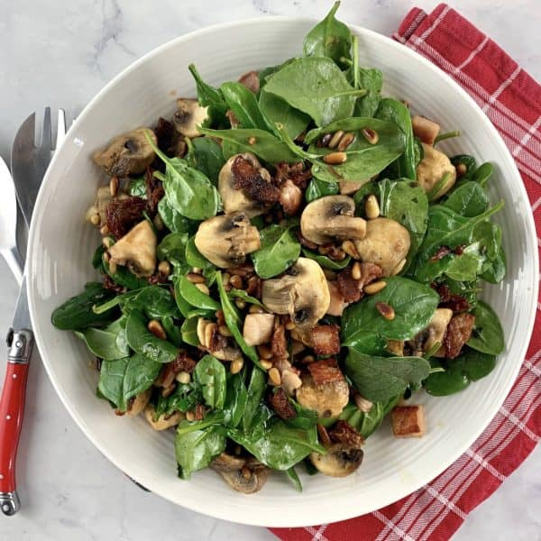 SPINACH MUSHROOM SALAD PORT IN WHITE BOWL WITH RED TEA TOWEL & RED SERVING SPOONS