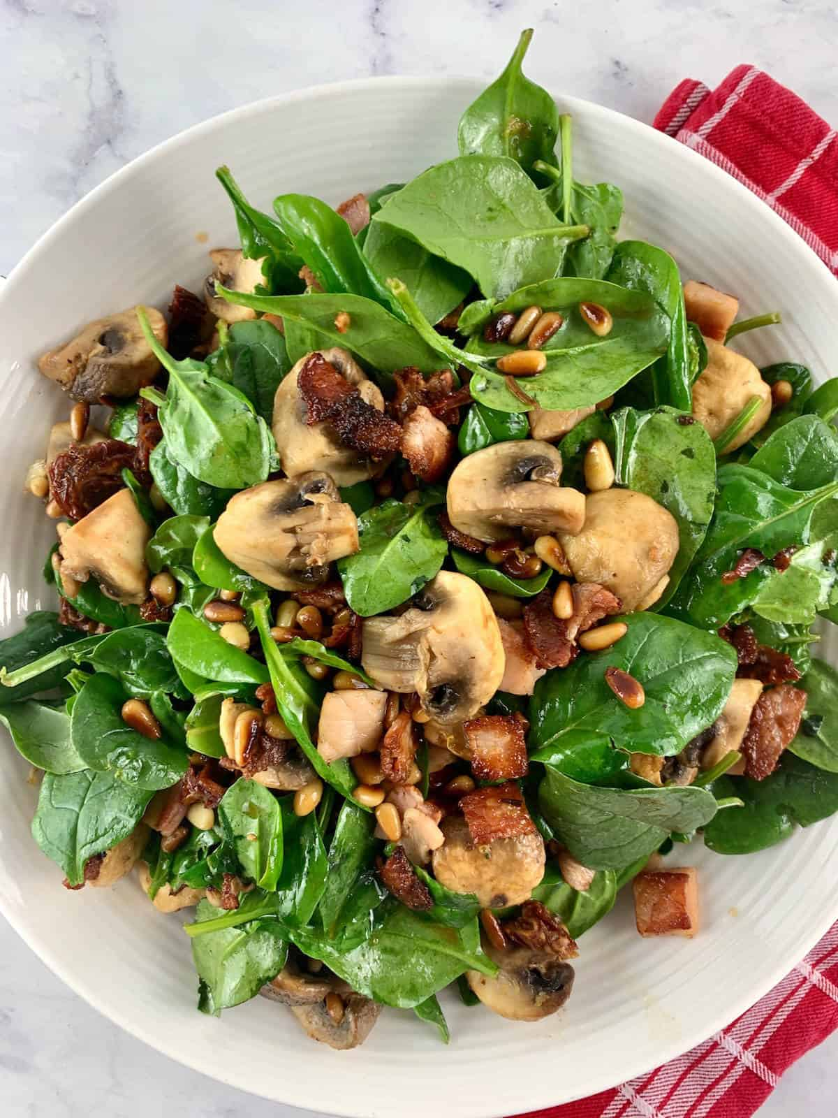 SPINACH MUSHROOM SALAD PORT IN WHITE BOWL WITH RED TEA TOWEL
