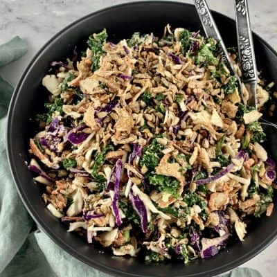 SUNFLOWER CRUNCH SALAD IN BLACK BOWL WITH SERVING SPOONS AND MINT GREEN SERVIETT ON THE SIDE