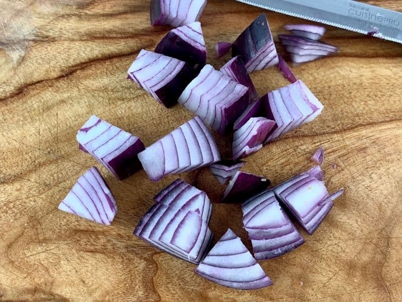 DICING RED ONION ON A WOODEN BOARD WITH A KNIFE
