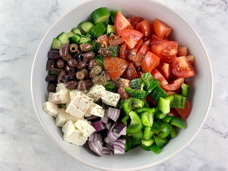 KETO GREEK SALAD INGREDIENTS IN MIXING BOWL