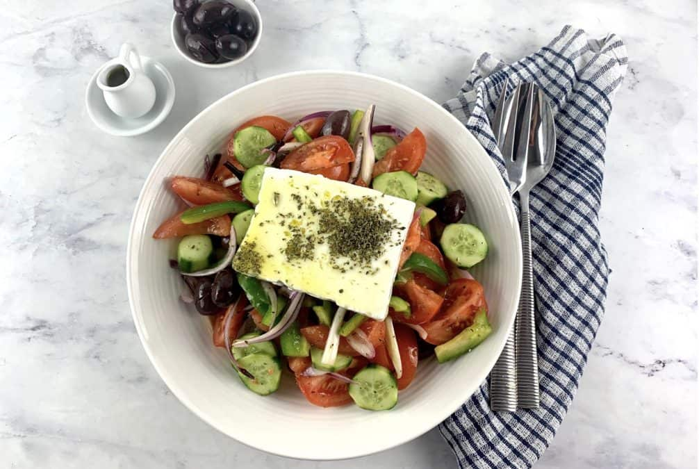 HORIATIKI SALATA IN A WHITE BOWL WITH OIL AND OLIVES ON THE SIDE