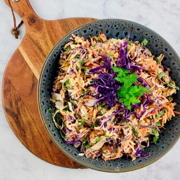 KETO COLESLAW IN A DARK GREY SALAD BOWL ON TOP OF A WOODEN BOARD WITH A RED CABBAGE PARSLEY GARNISH