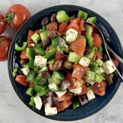 KETO GREEK SALAD IN A BLUE BOWL WITH SPOONS AND TOMATOES ON THE SIDE
