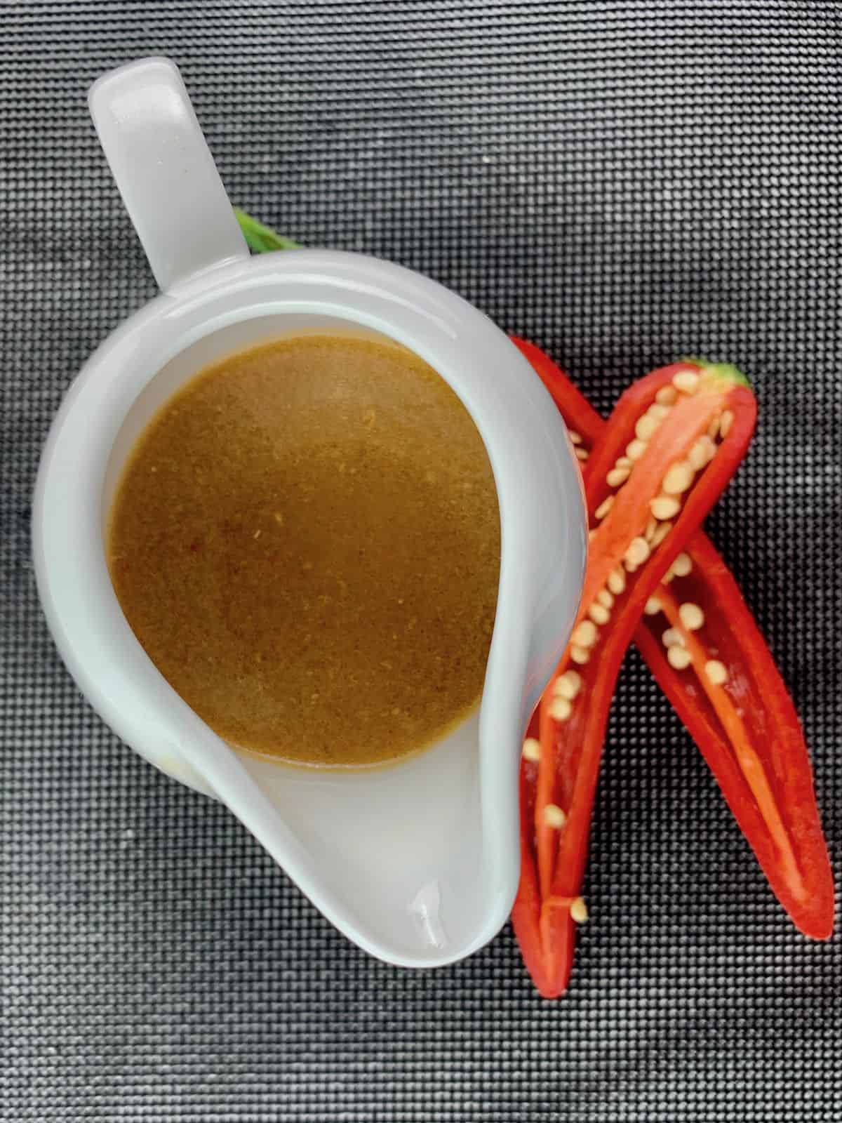 HARISSA VINAIGRETTE IN A WHITE JUG WITH CUT CHILLIS ON THE SIDE