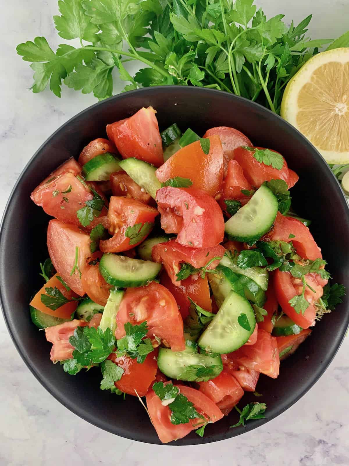 MEDITERRANEAN TOMATO CUCUMBER SALAD IN A BLACK BOWL WITH PARSLEY, LEMON AND GARLIC ON THE SIDE