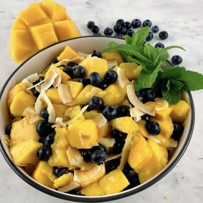 MANGO FRUIT SALAD WITH BLUEBERRIES & COCONUT IN A BOWL WITH MINT GARNISH & MANGO & BLUEBERRIES SURROUNDING