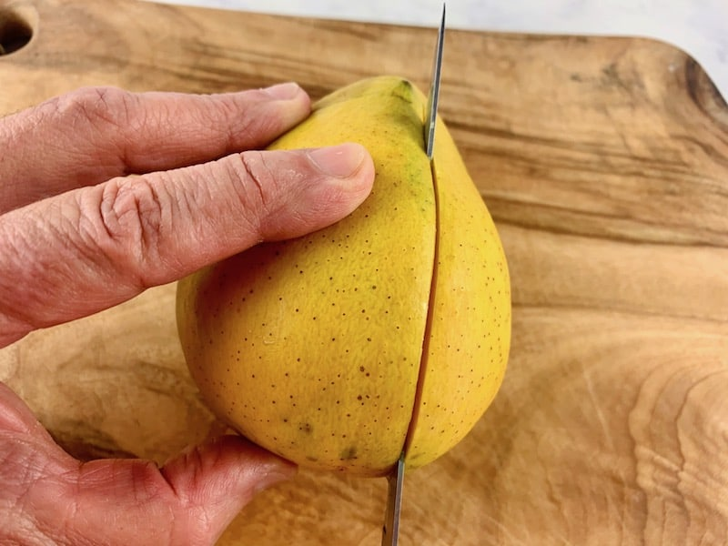 HANDS HOLDING MANGO AND SLICING CHEEK WITH A KNIFE ON A WOODEN BOARD