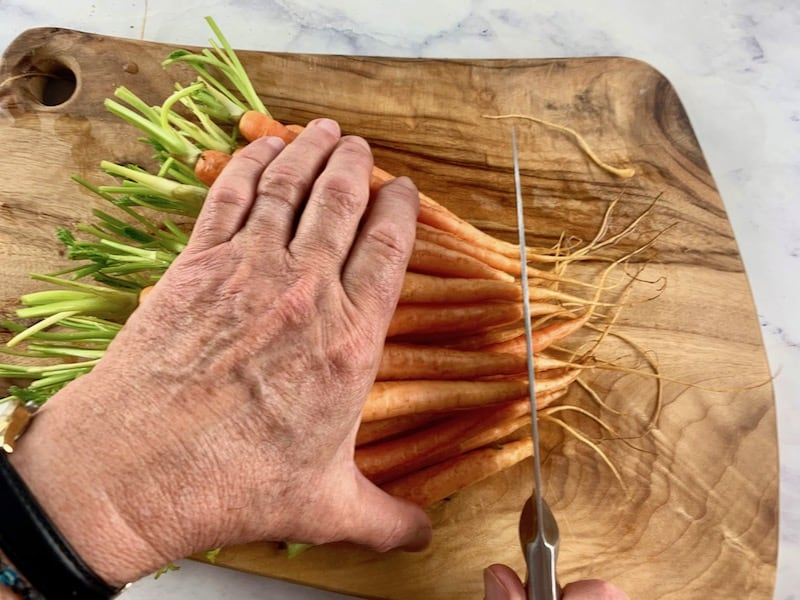 HANDS LINING BABY CARROTS UP ON A WOODEN BOARD TO BE TRIMMED WITH A KNIFE
