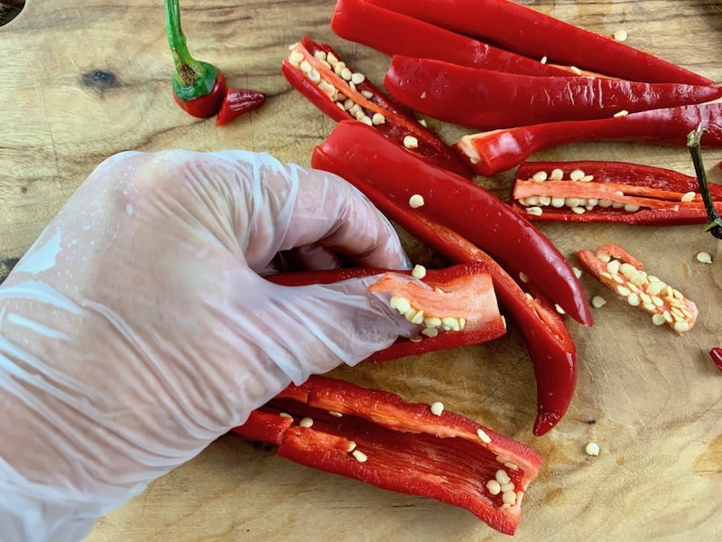 HANDS WEARING GLOVES REMOVING THE SEEDS FROM CHILLIS