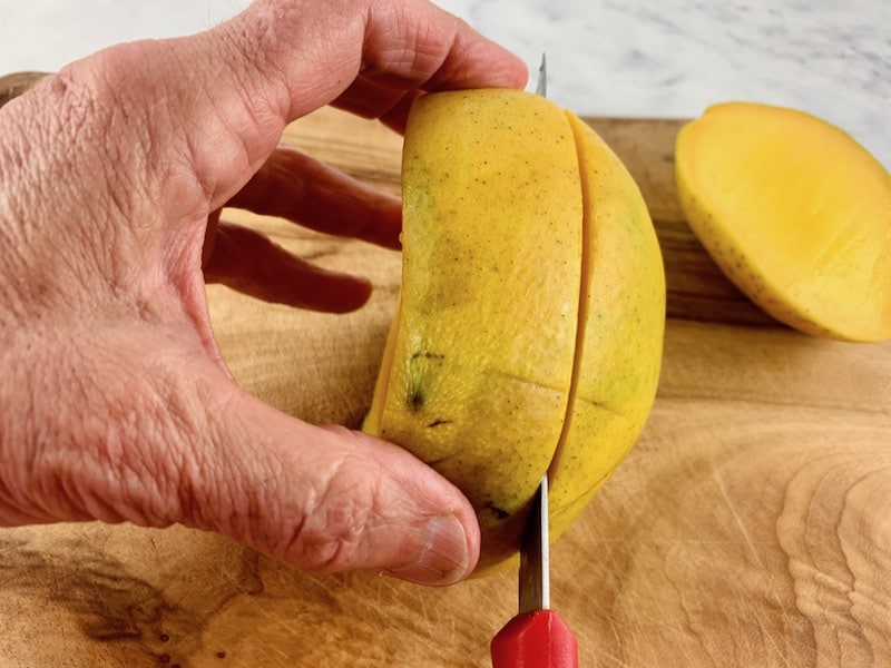 HANDS HOLDING MANGO AND SLICING 2ND CHEEK WITH A KNIFE ON A WOODEN BOARD
