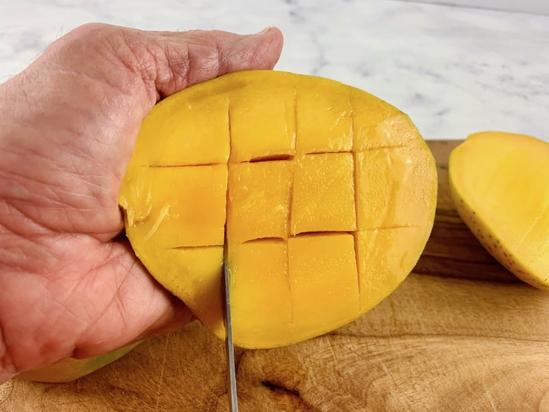 HANDS CUTTING MANGO FLESH INTO CROSS-HATCH PATTERN WITH A KNIFE ON A WOODEN BOARD