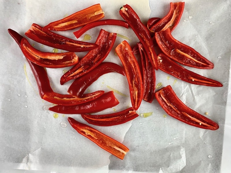 HALVED RED CHILLIS ON A BAKING TRAY WITH OIL & SALT