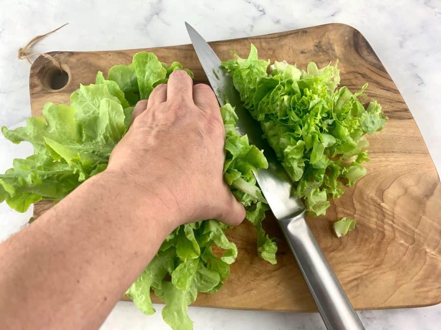 HANDS SHREDDING LETTUCE ON A WOODEN BOARD WITH A KNIFE