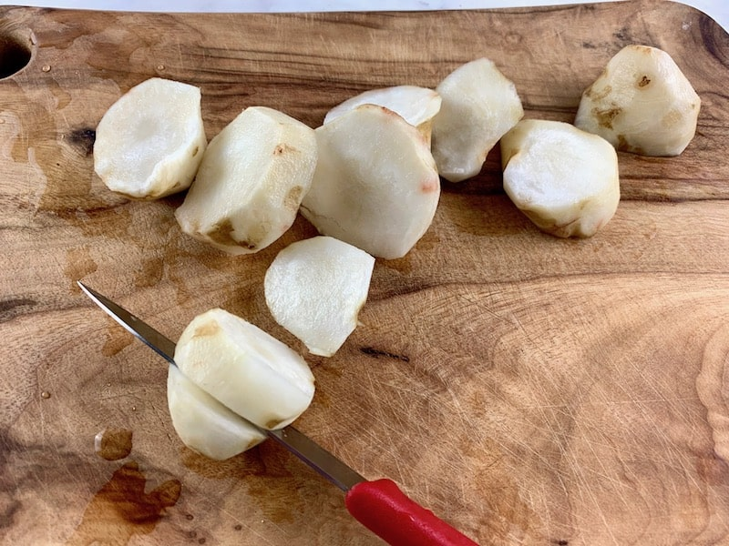 SLICING JERUSALEM ARTICHOKES ON WOODEN BOARD WITH RED KNIFE