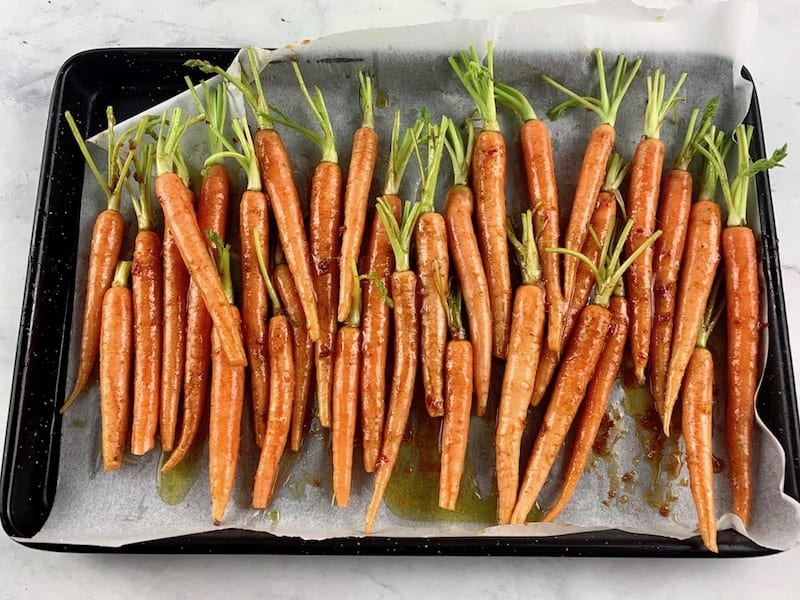 TRIMMED BABY CARROTS ON A LINED BAKING TRAY WITH SPICES AND OIL