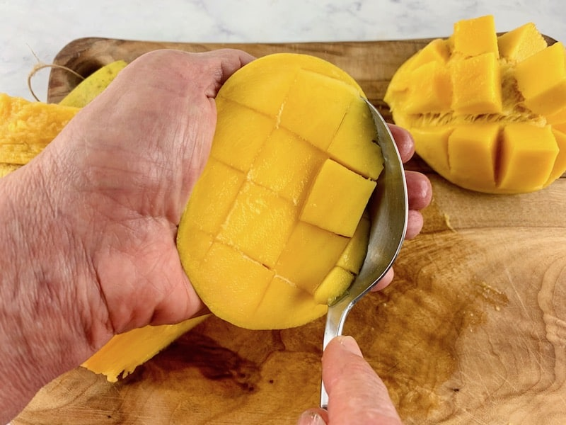 HANDS SCOOPING OUT MANGO FLESH WITH A SPOON ON A WOODEN BOARD