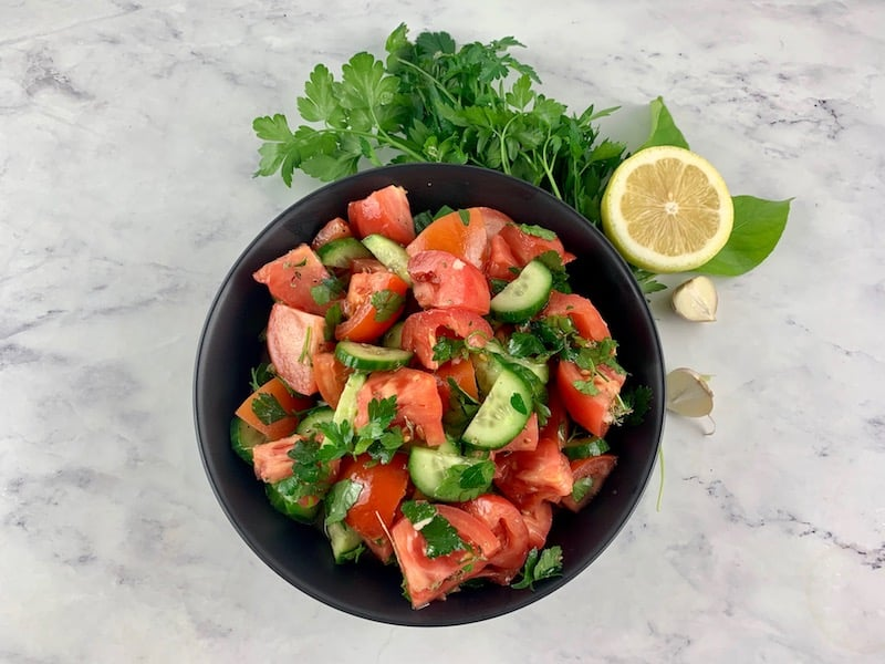 MEDITERRANEAN TOMATO TOMATO AND CUCUMBER SALAD IN A BLACK BOWL WITH PARSLEY, LEMON AND GARLIC ON THE SIDE