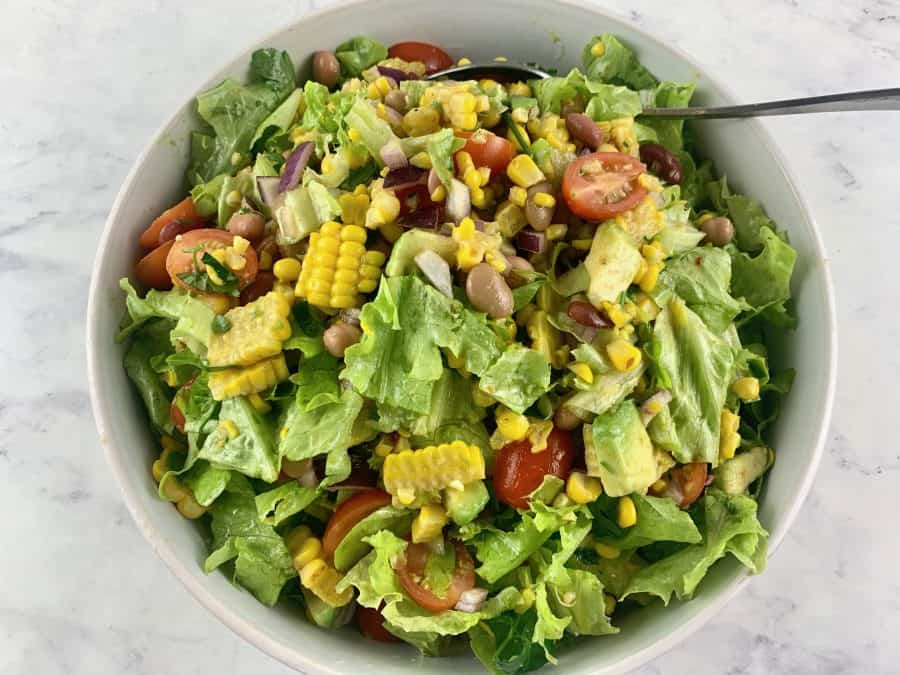 MIXING FIEST SALAD INGREDIENTS WITH DRESSING IN WHITE BOWL WITH SPOON