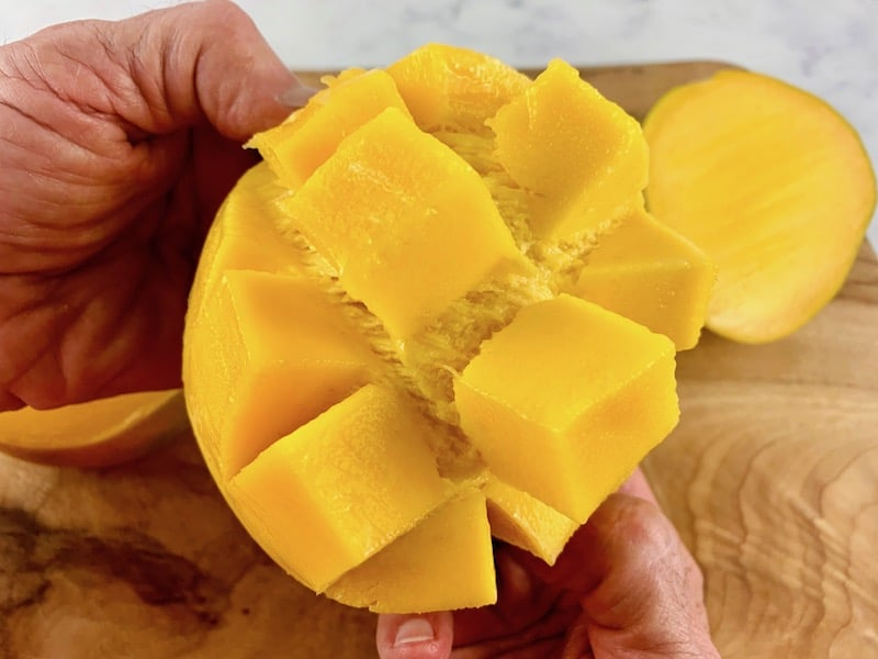 HANDS FLIPPING OUT DICED MANGO CHEEK ON WOODEN BOARD