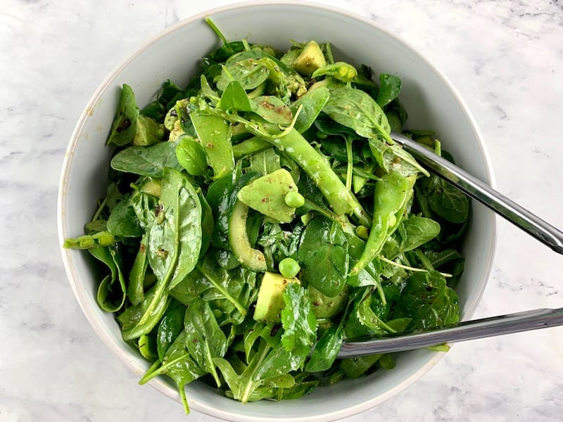 TOSSING SPINACH ARUGULA SALAD IN A WHITE BOWL WITH TONGS