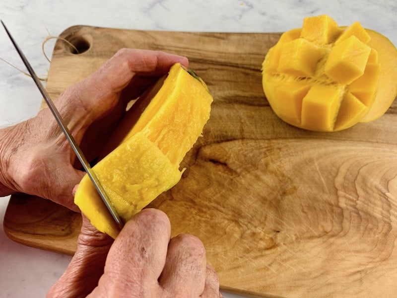 HANDS PEELING SKIN FROM MANGO SEED WITH A KNIFE ON WOODEN BOARD WITH DICED MANGO IN THE BACKGROUN
