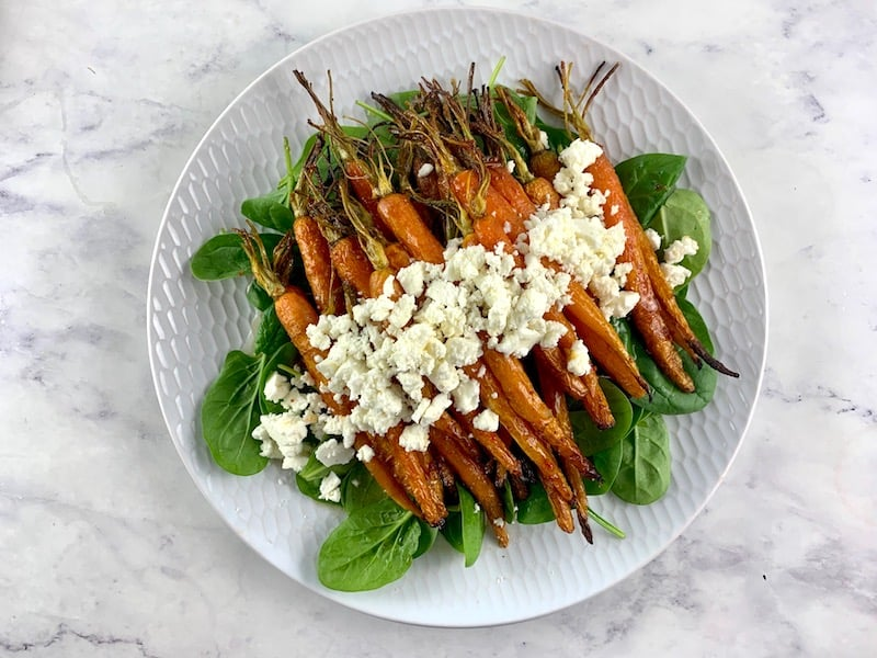 TOPPING SPINACH WITH ROASTED CARROTS AND FETA ON A WHITE PLATTER
