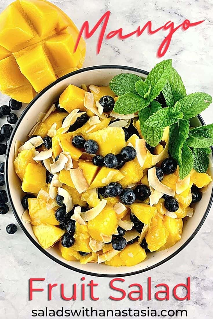 MANGO FRUIT SALAD WITH BLUEBERRIES & COCONUT IN A BOWL WITH MINT GARNISH & MANGO & BLUEBERRIES SURROUNDING WITH A TEXT OVERLAY