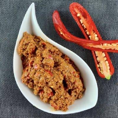 RAW HARISSA PASTE IN A WHITE BOWL WITH CUT RED CHILLIS ON THE SIDE