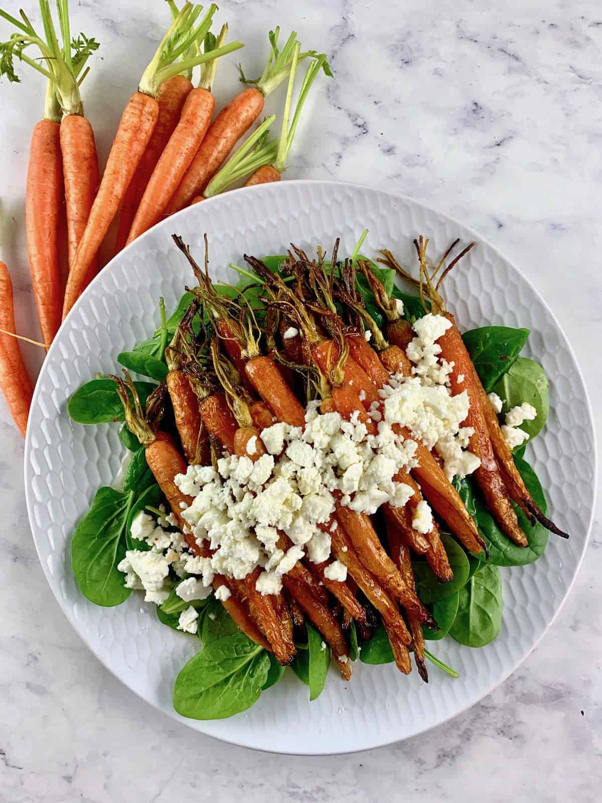 ROAST CARROT SALAD ON A WHITE PLATTER SURROUNDED ON ONE SIDE WITH BABY CARROTS