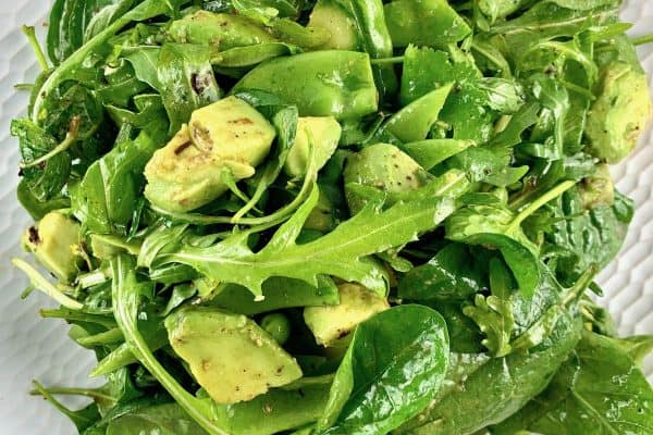 SPINACH ARUGULA SALAD ON A WHITE PLATE WITH GREENS SCATTERED AROUND
