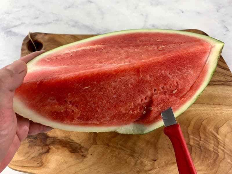 CUTTING RIND FROM WATERMELON WITH A KNIFE ON A WOODEN BOARD