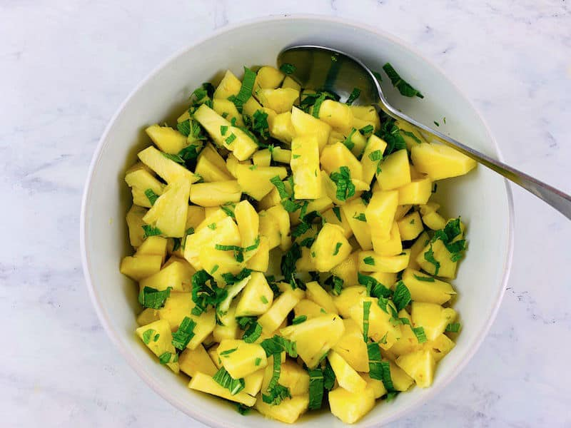 MIXING FRESH PINEAPPLE AND MINT SALAD IN A WHITE BOWL WITH A SPOON