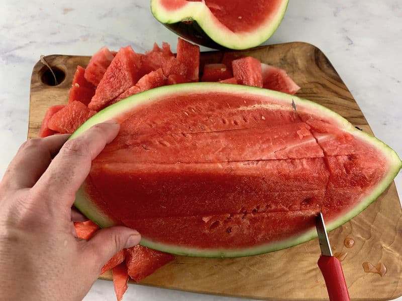 SLICING WATERMELON ON A WOODEN BOARD WITH A KNIFE