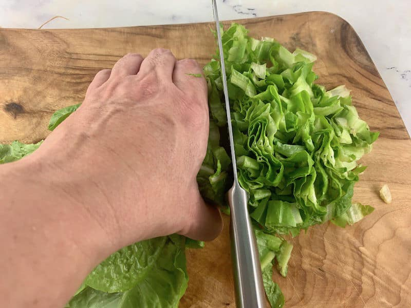 SHREDDING LETTUCE ON A WOODEN CHOPPING BOARD WITH A KNIFE