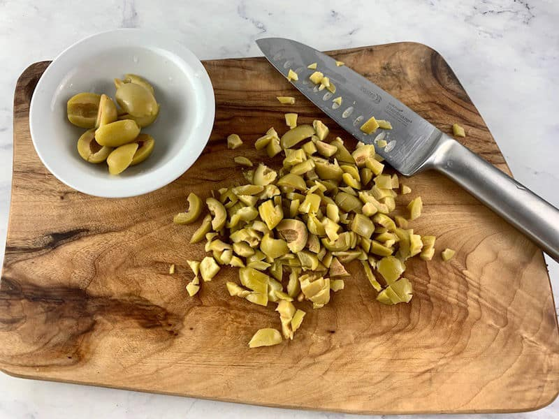 CHOPPED GREEN OLIVES ON A WOODEN BOARD WITH A KNIFE AND HALVED OLIVES IN A WHITE DISH