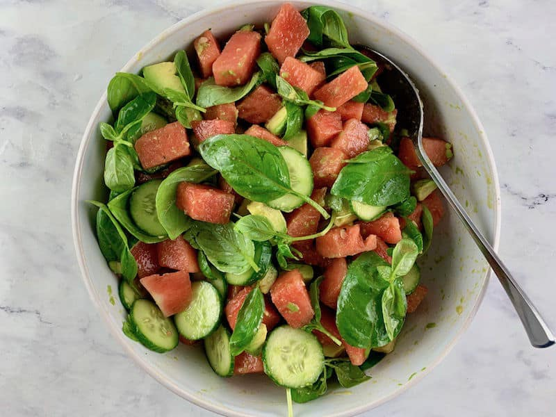MIXING WATERMELON AVOCADO SALAD WITH A SPOON IN A WHITE BOWL