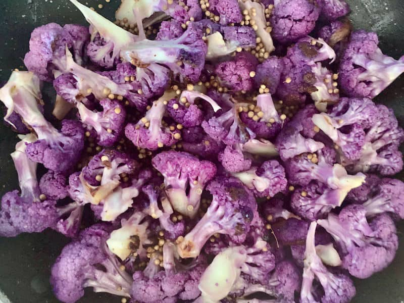 ADDING CORIANDER SEEDS TO PAN WITH PURPLE CAULIFLOWER
