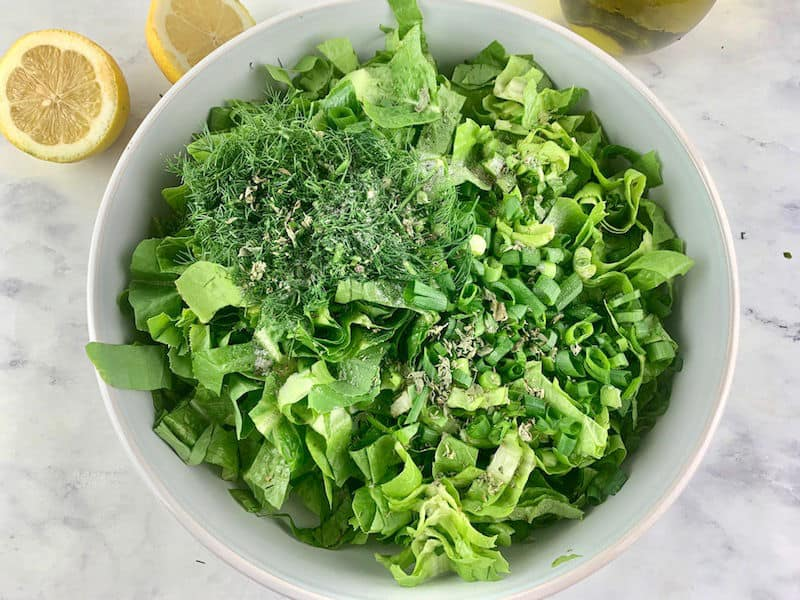 MAROULOSALATA INGREDIENTS IN A WHITE BOWL WITH CUT LEMONS & OLIVE OIL ON THE SIDE