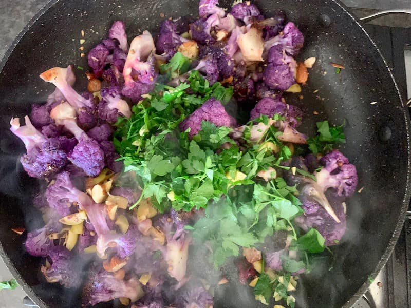 ADDING PARSLEY TO PAN WITH REMAINING PURPLE CAULIFLOWER SALAD INGREDIENTS