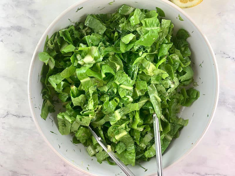 TOSSING MAROULOSALATA IN A WHITE BOWL TO COMBINE