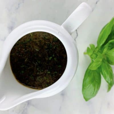 BASIL BALSAMIC VINAIGRETTE IN A WHITE JUG WITH A SPRIG OF BASIL ON THE SIDE