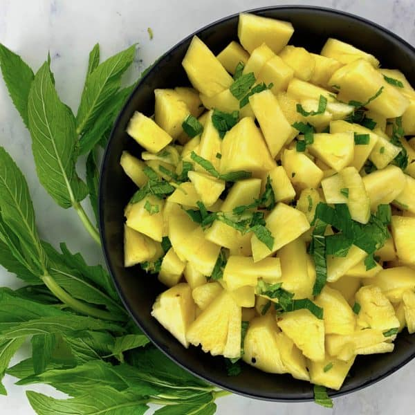 FRESH PINEAPPLE & MINT SALAD IN A BLACK BOWL WITH MINT LEAVES ON THE SIDE