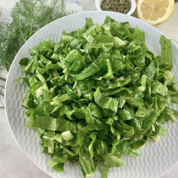 MAROULOSALATA IN A WHITE PLATTER WITH FRESH DILL, DRIED OREGANO, CUT LEMONS & OLIVE OIL ON THE SIDE