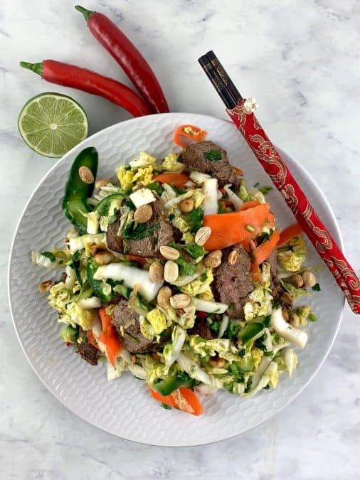 VIETNAMESE BEEF SALAD ON A WHITE PLATE WITH CHOPSTICKS, LIME AND CHILLI ON THE SIDE